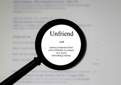 Selective focus on word unfriend, word in a dictionary. Close up of an English dictionary page with word unfriend.