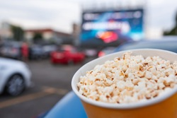 Selective focus on yellow bucket full of popcorn on car parking at drive-in cinema background. Free time, leisure and entertainment concept