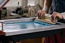 selective focus photo of male hands with squeegee. serigraphy production. printing images on t-shirts by silkscreen method in a design studio