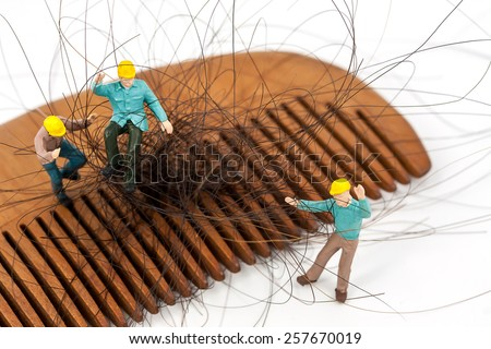selective focus photo of miniature workers holding hair loss from wooden comb, abstract background to solution hair loss concept.
