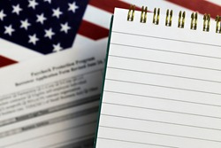 selective focus photo of open notepad with blank space, on a background of paycheck protection program borrower application form and the United States flag. paycheck protection program new round
