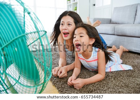 selective focus photo of sweet woman and happy little girl playing electric fan and blowing cool wind at home for eliminating summer heat.