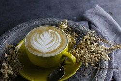 selective focus picture, latte art coffee served in yellow cups and old trays (still life foodphotography