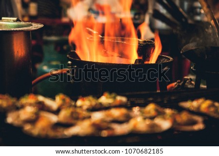 Selective focus picture of some Grilled scallops sold at a street market stall with a pan covered with flames on the background. Chinatown, Bangkok, Thailand