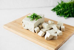 selective focus piece of tofu cheese with herbs cut into many small cubes on bamboo cutting board in white kitchen, healthy vegan food content