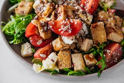 selective focus recipe for healthy diet salad of tofu cheese, tomatoes, eggs, dressing, sesame seeds and seeds. vegetarian food content, close-up