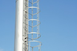 Selective focus, safety ladder at stadium light pole for prevent accident while climbing up for maintenance. Clear blue sky background. Concept of safety first, safety equipment, stadium light pole.
