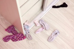 Selective focus.  Socks are scattered near the open closet in the girl's room. Untidy clothes. The concept of disorder, sloppiness.