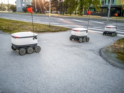 Selective focus. Some Delivery robots on the street. Estonian Cyber-couriers in Tallinn city. Sunny summer day. Copy space. Fitered image. the concept of new technology.