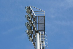 Selective focus, structure underneath stadium light pole, metal fence and metal floor, rest area for maintenance lighting equipment. Safety ladder beside pole for safety.