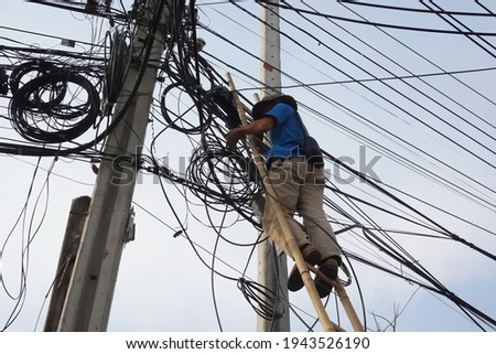 Selective focus technician man stands on ladder without safety belt is risk work while fixing fiber optical cable. Unsafe workplace, risk work, unsafe acts concept.                                 Foto stock ©