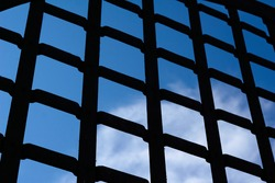 Selective focus, texture of a metal old lattice fence against the blue sky, fence lattice, lattice background, cell. High quality photo
