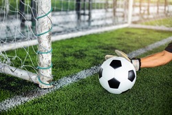 Selective focus to goal post with soccer ball in hand of goalkeeper on artificial turf.