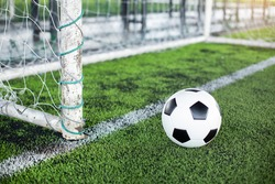 Selective focus to goal post with soccer ball on artificial turf.