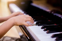 Selective focus to kid fingers and  piano key to play the piano. There are musical instrument for concert or learning music. Close up hand of child musician playing the piano on stage