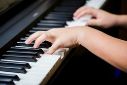 Selective focus to kid fingers and  piano key to play the piano. There are musical instrument for concert or learning music. Close up hand of child musician playing the piano on stage.