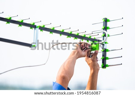 Selective focus to The digital TV antenna with the hands of a technician is installing. Stock fotó ©