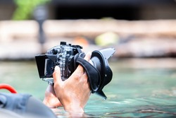 Selective focus to the underwater camera in the hands of a photographer in a pond.