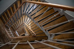 Selective focus to vintage spiral stairs of antique building. French style architectural details of stairway with wooden steps and ornate metal railings