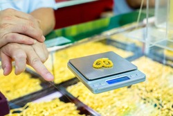 Selective focus to weighing gold jewelry with small digital scales in gold jewelry shop. Yaowarat gold shop, Thailand.