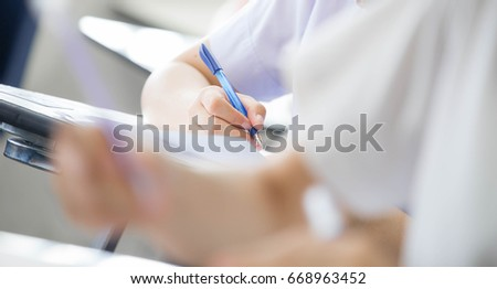 selective focus university or high school student holding pencil.sitting on row chair writing final exam in examination room or study in classroom.student in uniform.space for text.education concept