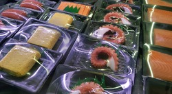 Selective focus view of ready-to-eat packed Japanese food (raw salmon, tuna, grill octopus, rolled egg or rolled omelette, crab stick) in the local store or grocery store.