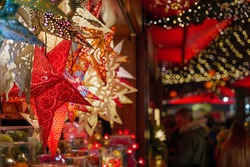 Selective focus view of star cut-out paper hanging lantern in front of stall during Christmas market in Germany with blur background with bokeh of illuminated night atmosphere.