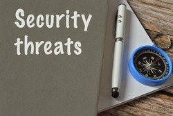 Selective focus with noise effect of pen, compass and notebook written with text SECURITY THREATS.