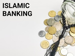 Selective focus with noise effect phrase ISLAMIC BANKING with coins spilled from a glass jar and rosary isolated on white background.Islamic finance concept.