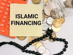 Selective focus with noise effect phrase ISLAMIC FINANCING on paper note with coins spilled from a glass jar,calculator and rosary isolated on white background.Islamic finance concept.