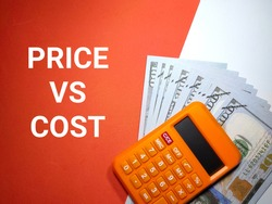 Selective focus.Word PRICE VS COST with calculator and banknote on a white and red background.Business concept,shot were noise and grain.