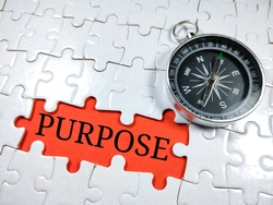 Selective focus.Word PURPOSE with compass on jigsaw puzzle and red background.Business concept.