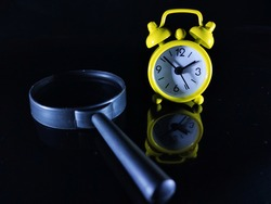 Selective focus.Yellow clock and magnifying glass on a black background.Shot were noise and film grain in full resolution.