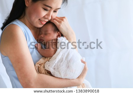 Selective focus young Asian beautiful mother hold newborn baby 0-1 month in her arms with love, gently, infant happy sleeping mom looking infant , newborn baby feeling secure while sleeping in mom arm