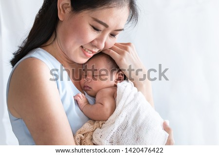 Selective focus young Asian beautiful mother hold newborn baby 0-1 month in mom arms with love, gently, infant happy sleeping mom looking infant , newborn baby feeling secure while sleeping comforting