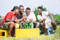selective focuse of cheerful african guys, looking on smart phone, with bottles infront- outdoor concept
