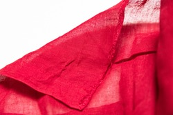 Selective focuse. Red cambric fabric with a wrapped corner and a criss-cross texture.