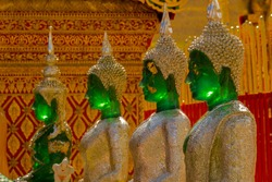 selective focused image of tidily ancient green buddha statues (selectived focused at right second buddha) in temple at Wat Phra That Doi Suthep or Phra That Doi Suthep temple in Chiang Mai, Thailand
