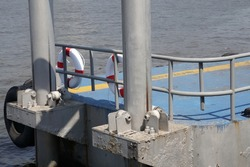 Selective focused, metal pillars installed in river support steel pier for floating. Lifebuoy hanging on fence for rescue. Yellow line safety zone on floor. River in back.