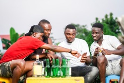 selective focused of cheerful african guys, looking on smart phone, with bottles infront- outdoor concept