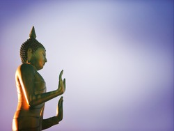Selective focused photo of a Buddha image icon raising both hands with vignette with space for runaround or wraparound text