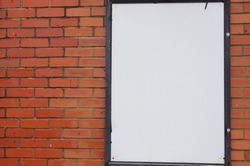 Selective focused photo of a white board on red brick background with space for runaround or wraparound text