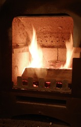 Selective focused portrait orientation photo of flame in a wood stove with copyspace for runaround or wraparound text