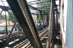 Selective focused, steel bridge of railway tracks for train crossing canal in Bangkok. Canal, building tree background. Concept of steel bridge, railway tracks, train tracks, vintage bridge.