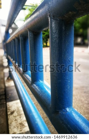 Selective focusing on Blue safety rail barrier along the walkway with perspective and soft focus background