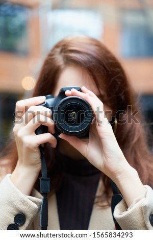 Selective focuson lens. Beautiful stylish fashionable girl holds camera in her hands and takes pictures. Woman photographer with long dark hair in a city, urban shoot, vertical. unrecognizable person #1565834293
