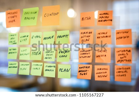 Self adhesive notes with slogans (words) stuck on the glass in the office. Brainstorming concept.