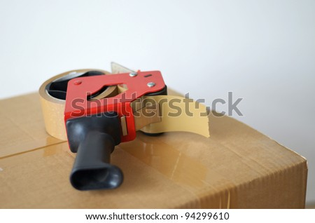 Self-adhesive tape dispenser on brown cardboard box