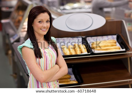 Self-assured female cook smiling at the camera in front of her bakery