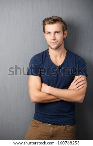 Self-assured handsome man standing with his arms crossed in smart casual clothing against a dark studio background
